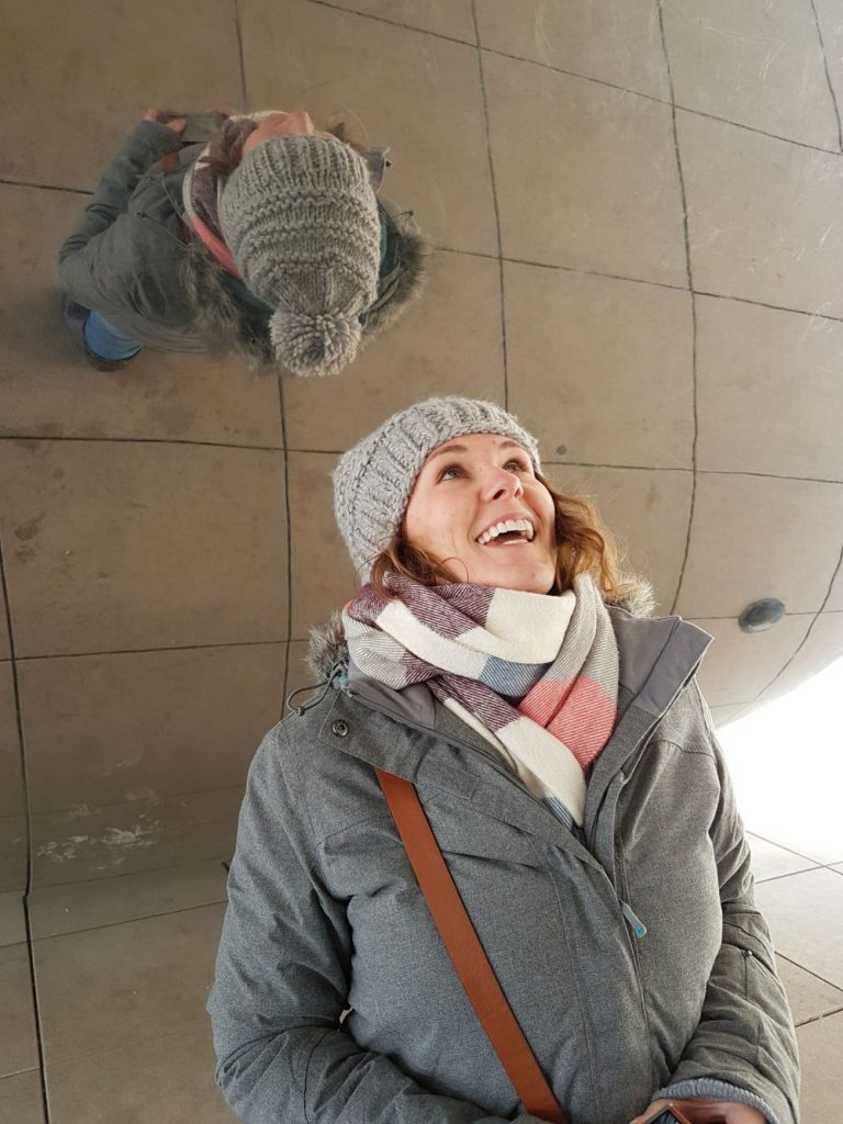 Amy at Hey Me in a hat and scarf looking up at a reflection on a mirrored ceiling