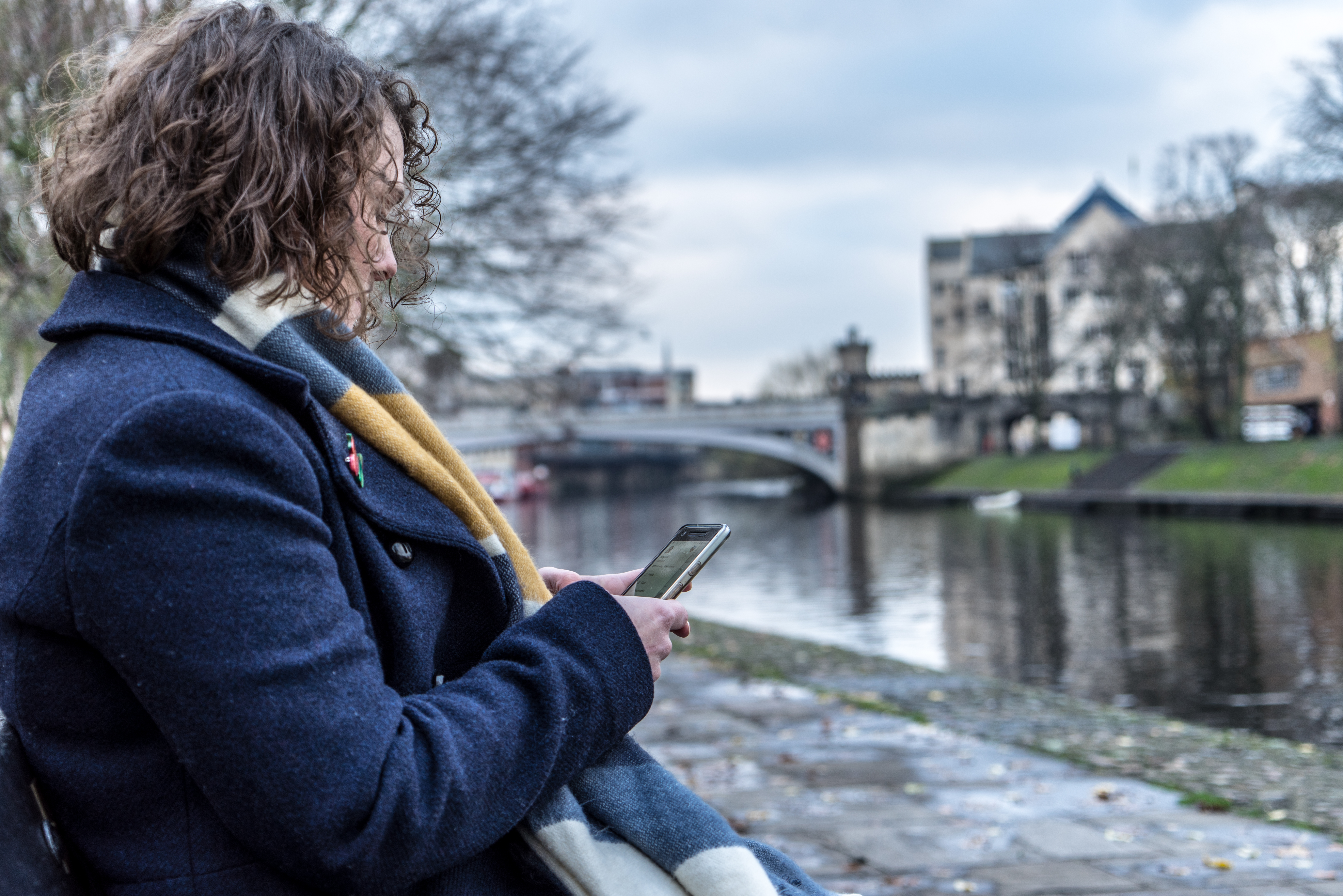 Amy sits on a bench overlooking the river ouse, using her phone