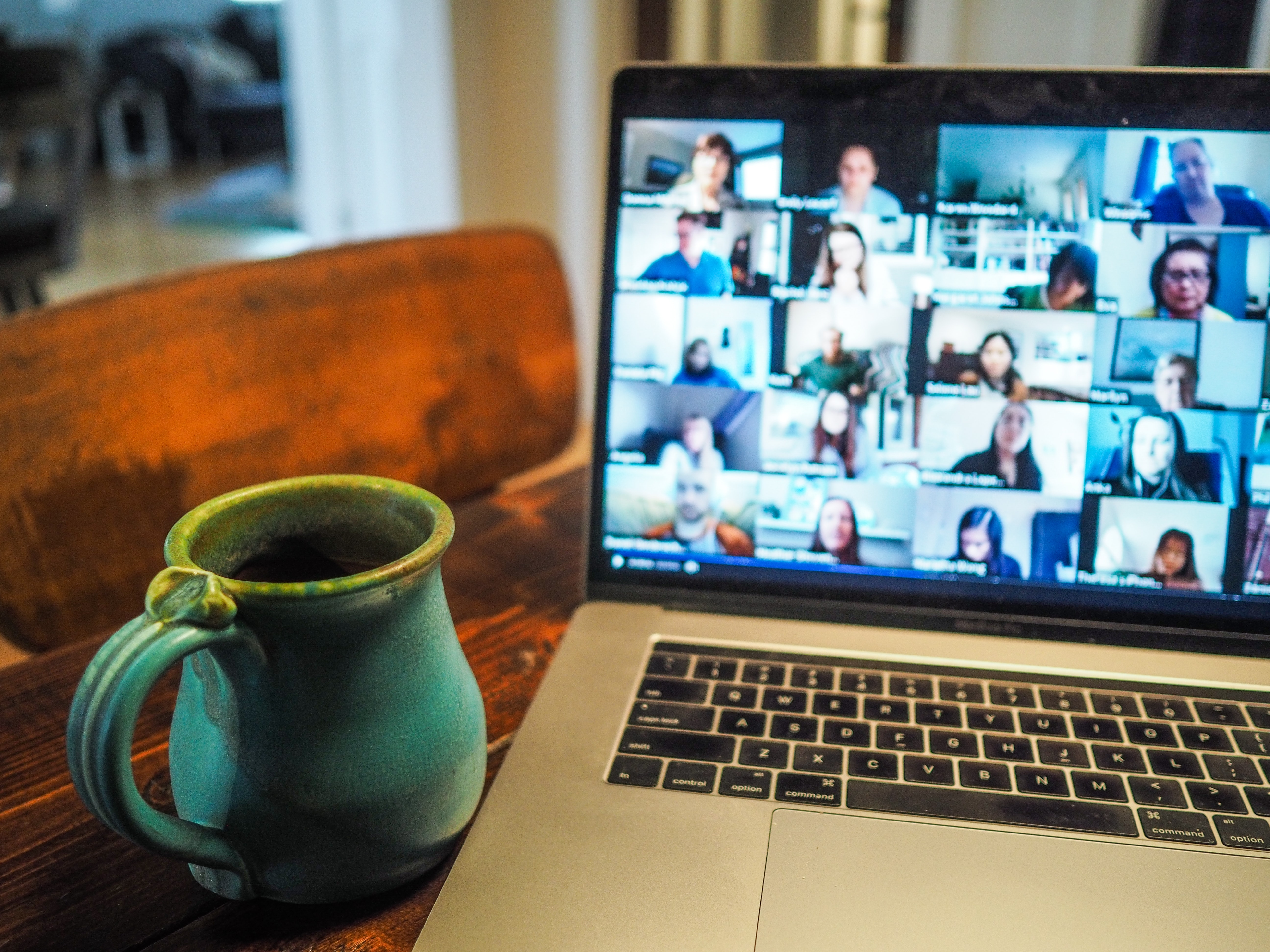 A mug on a desk, with a laptop displaying a Zoom call