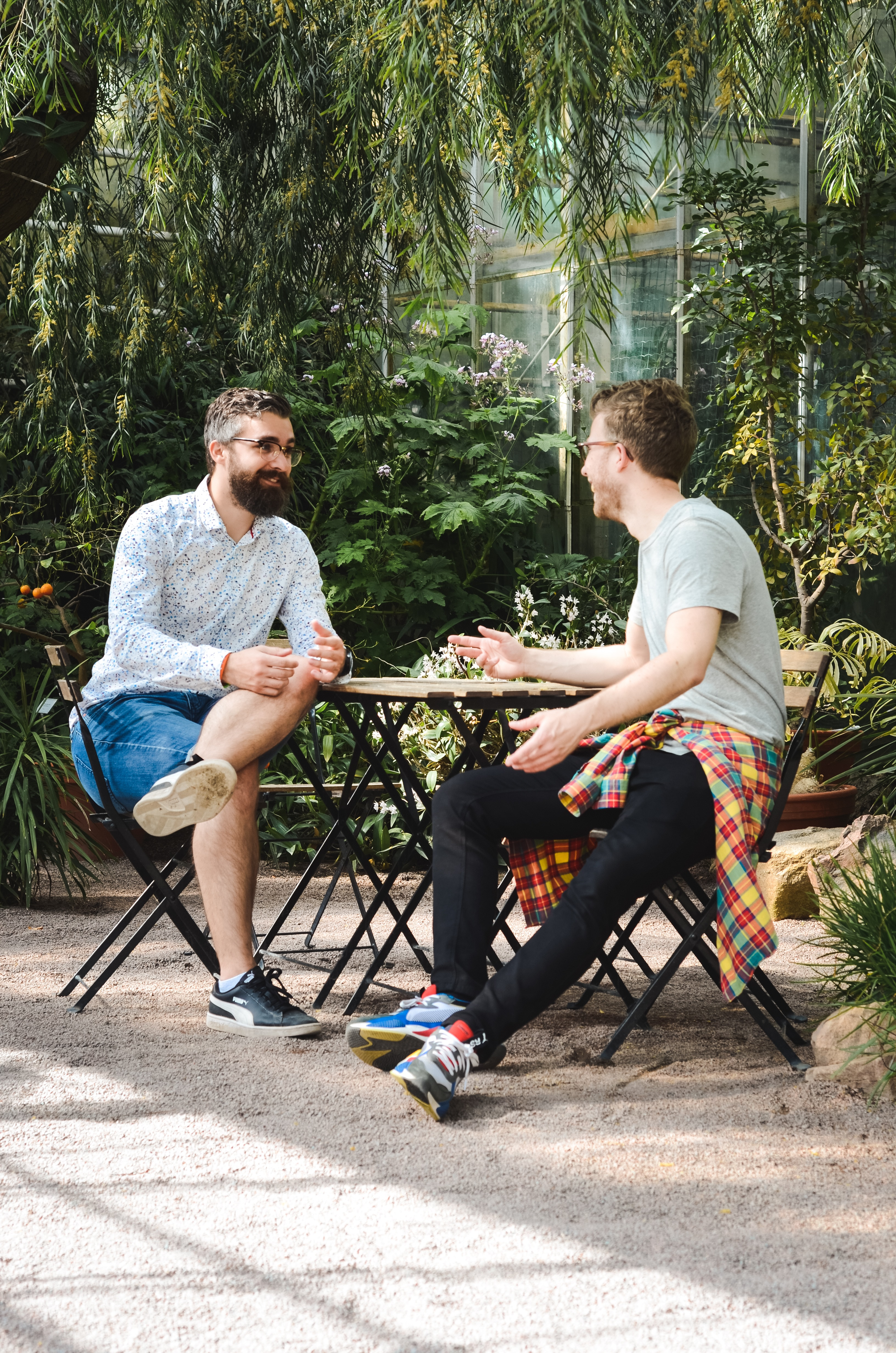 Two men sit at a table outside talking