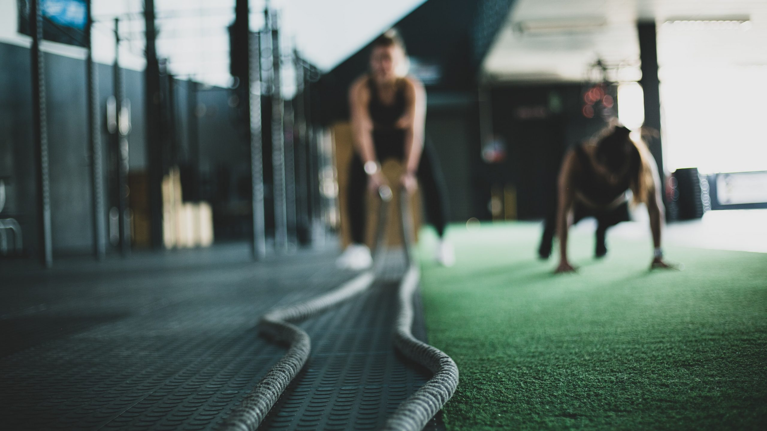 Two people exercising in a gym using ropes