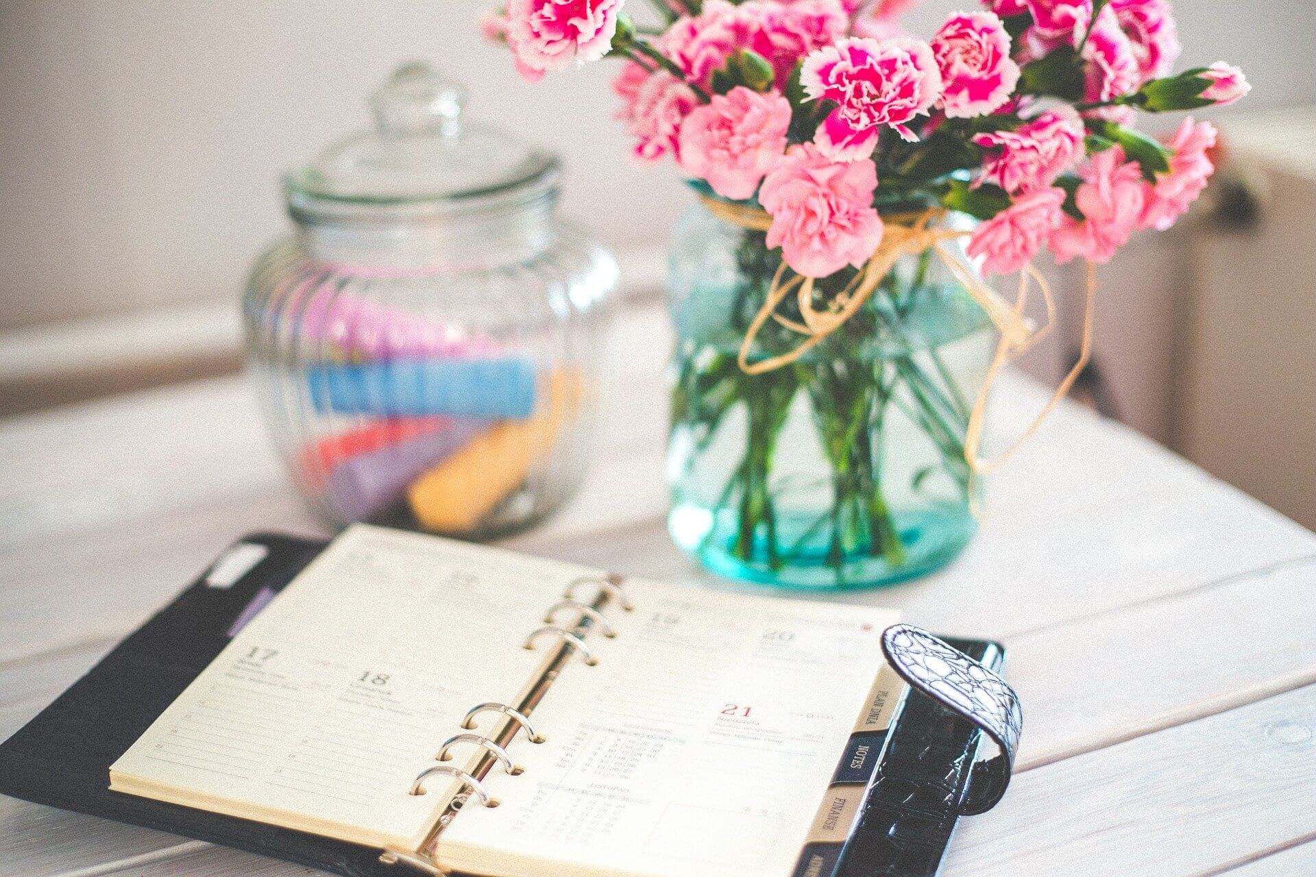 A planner sits open on a desk beside some flowers
