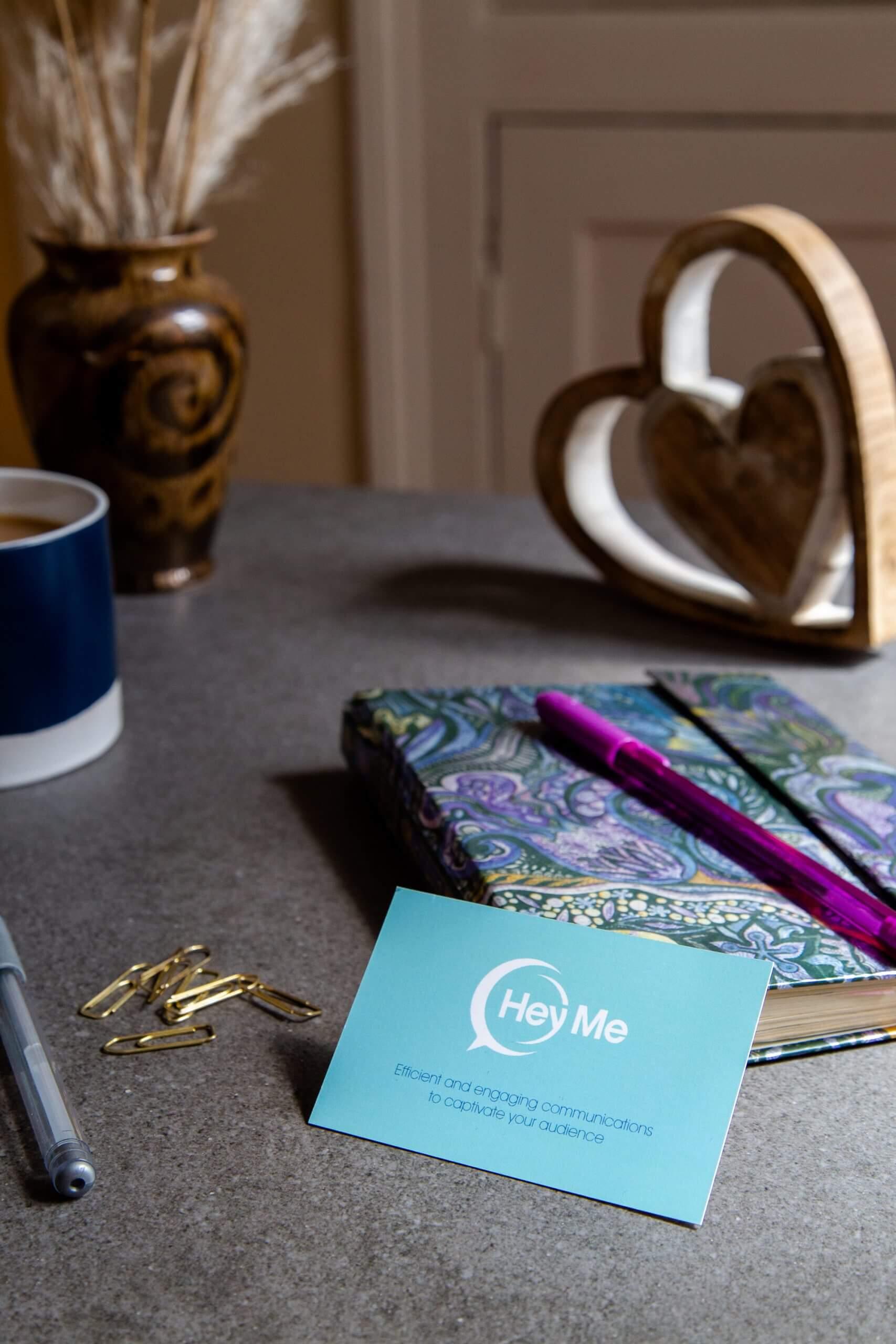 Hey Me business card, mug and notepad on a desk