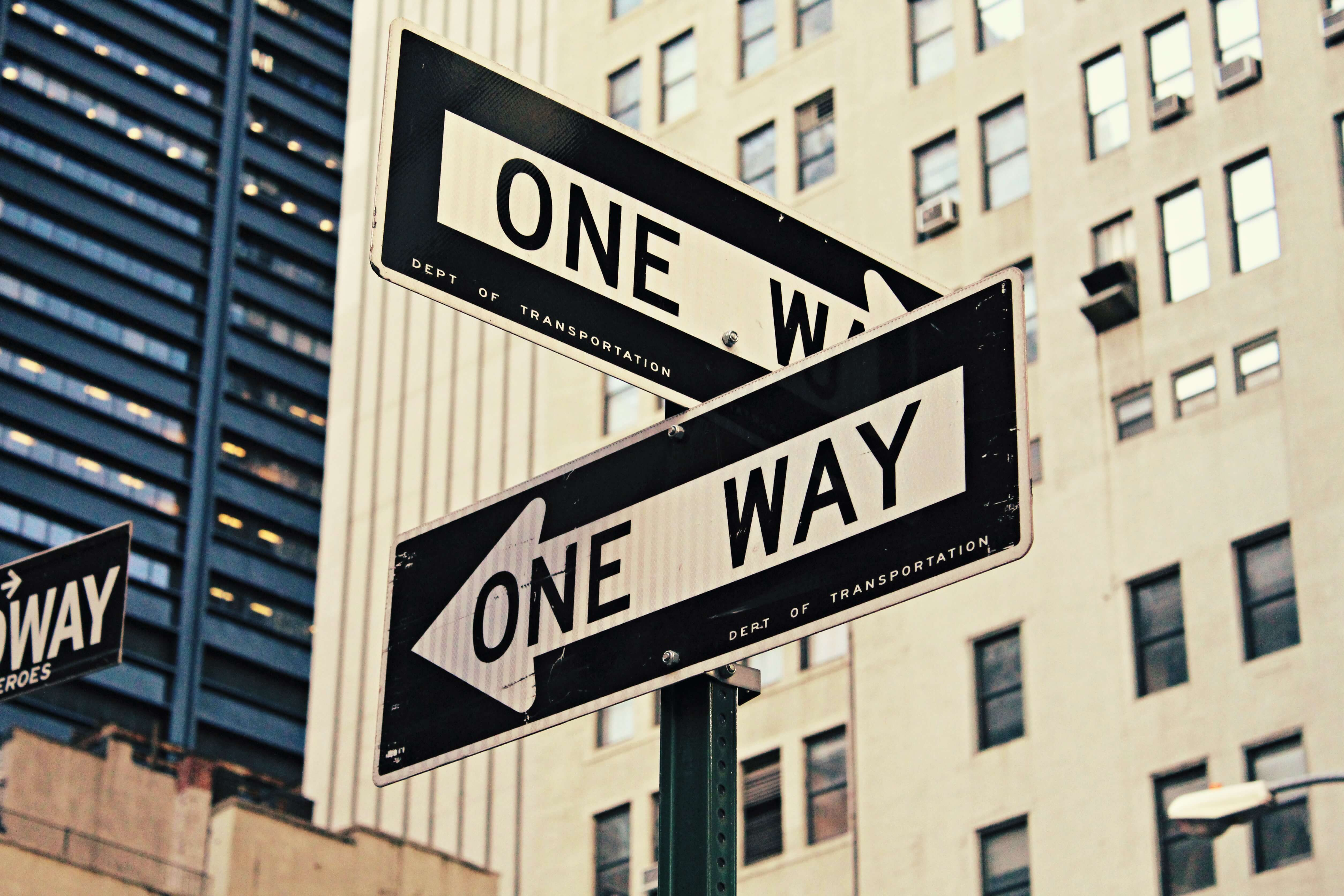 Two signs saying one way