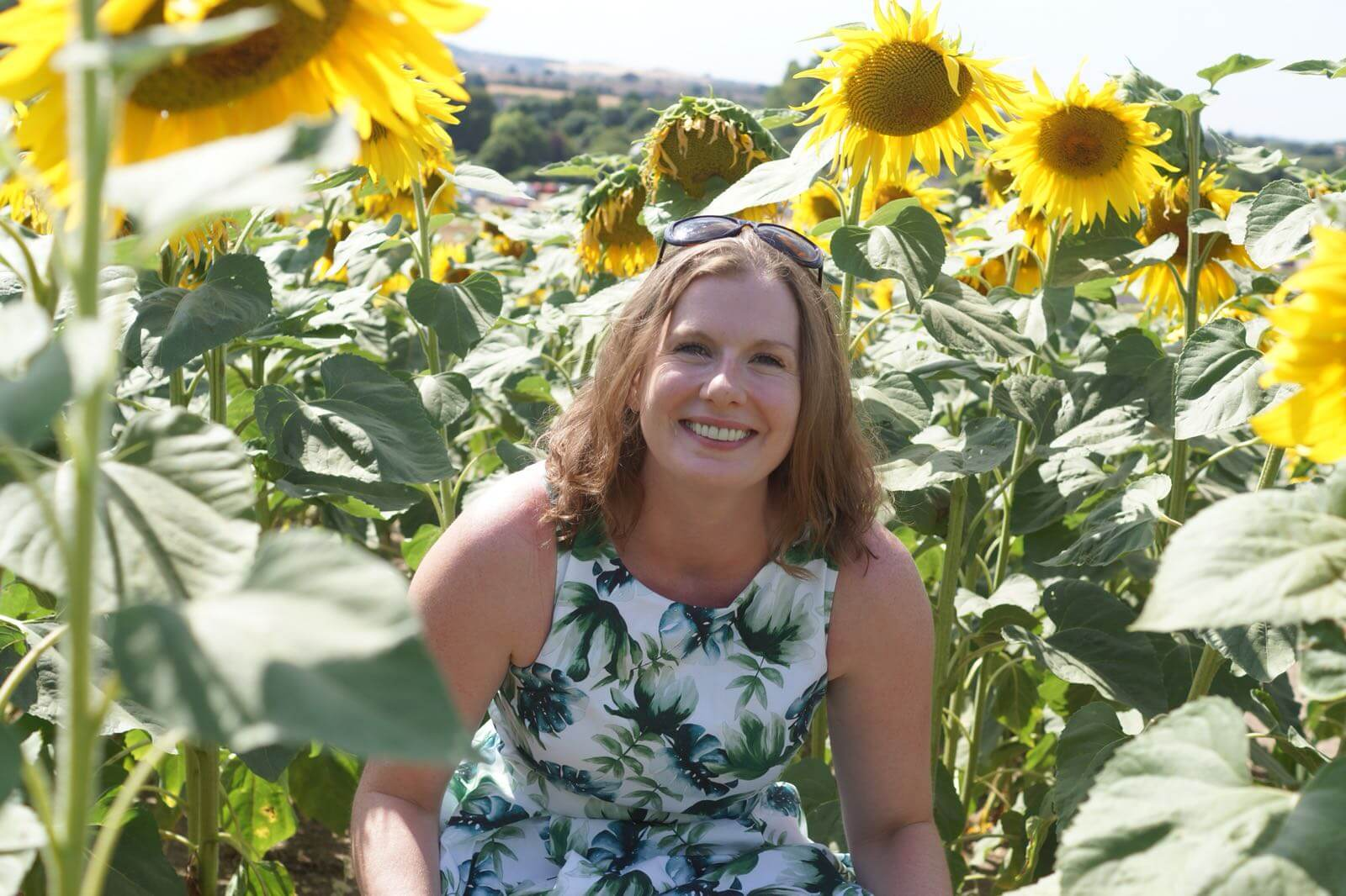 Stephanie smiling beside sunflowers