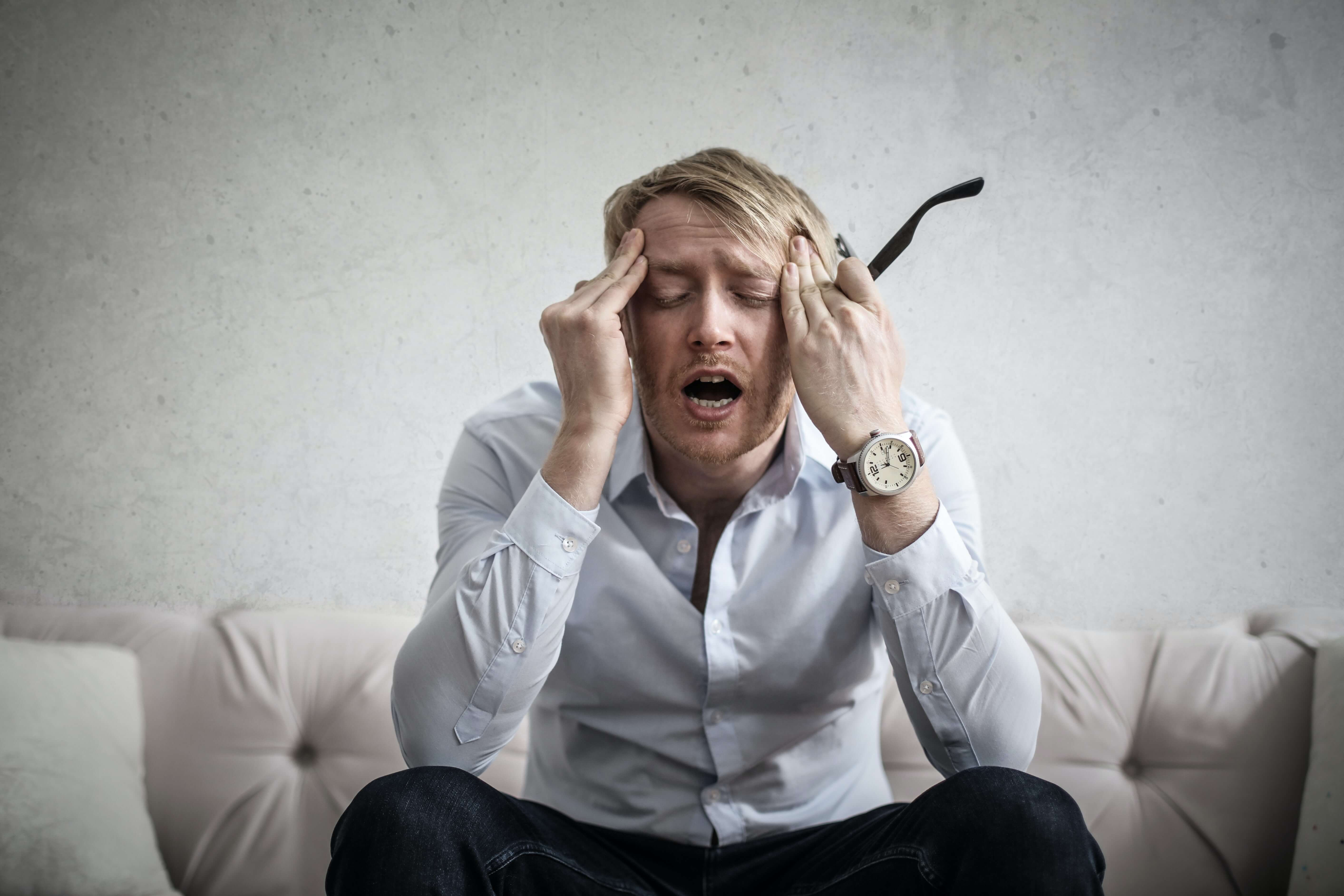 Man puts his hands on his head in frustration