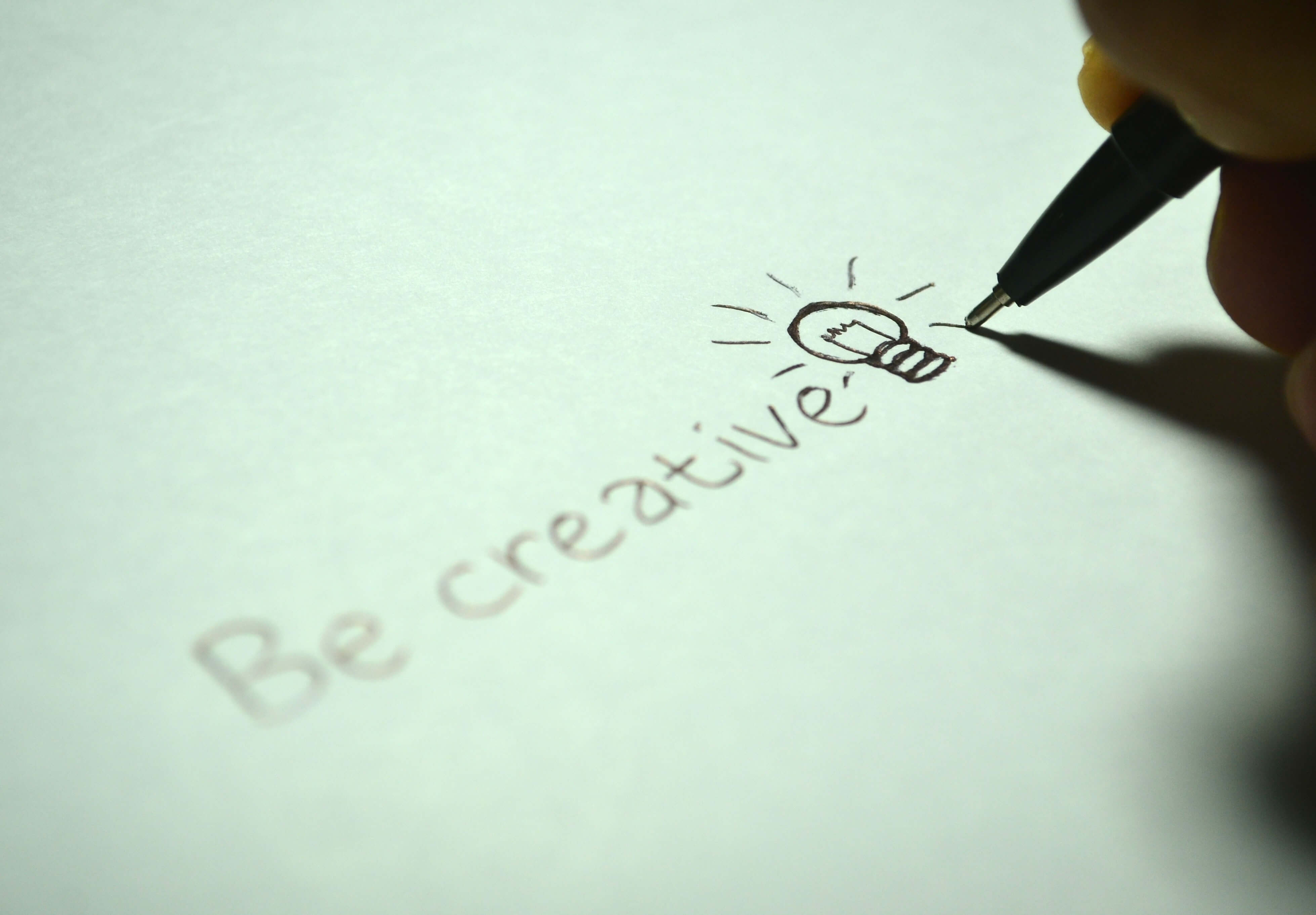Person writing 'be creative'