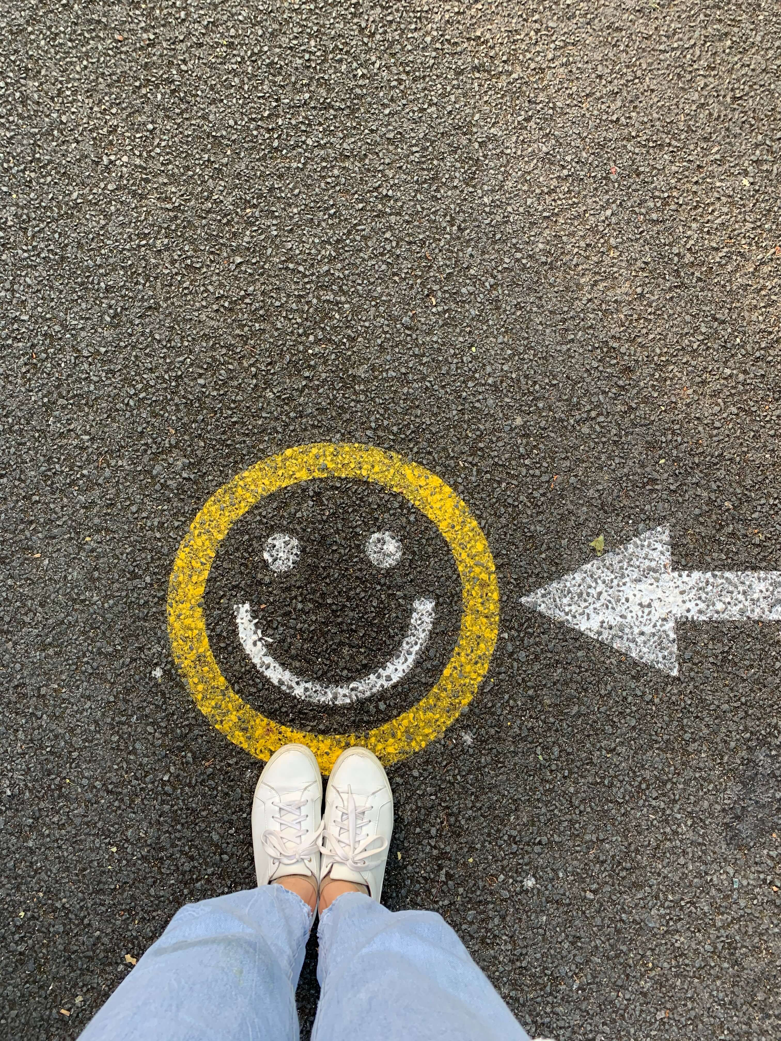 Person with feet pointing towards smiley face on the ground