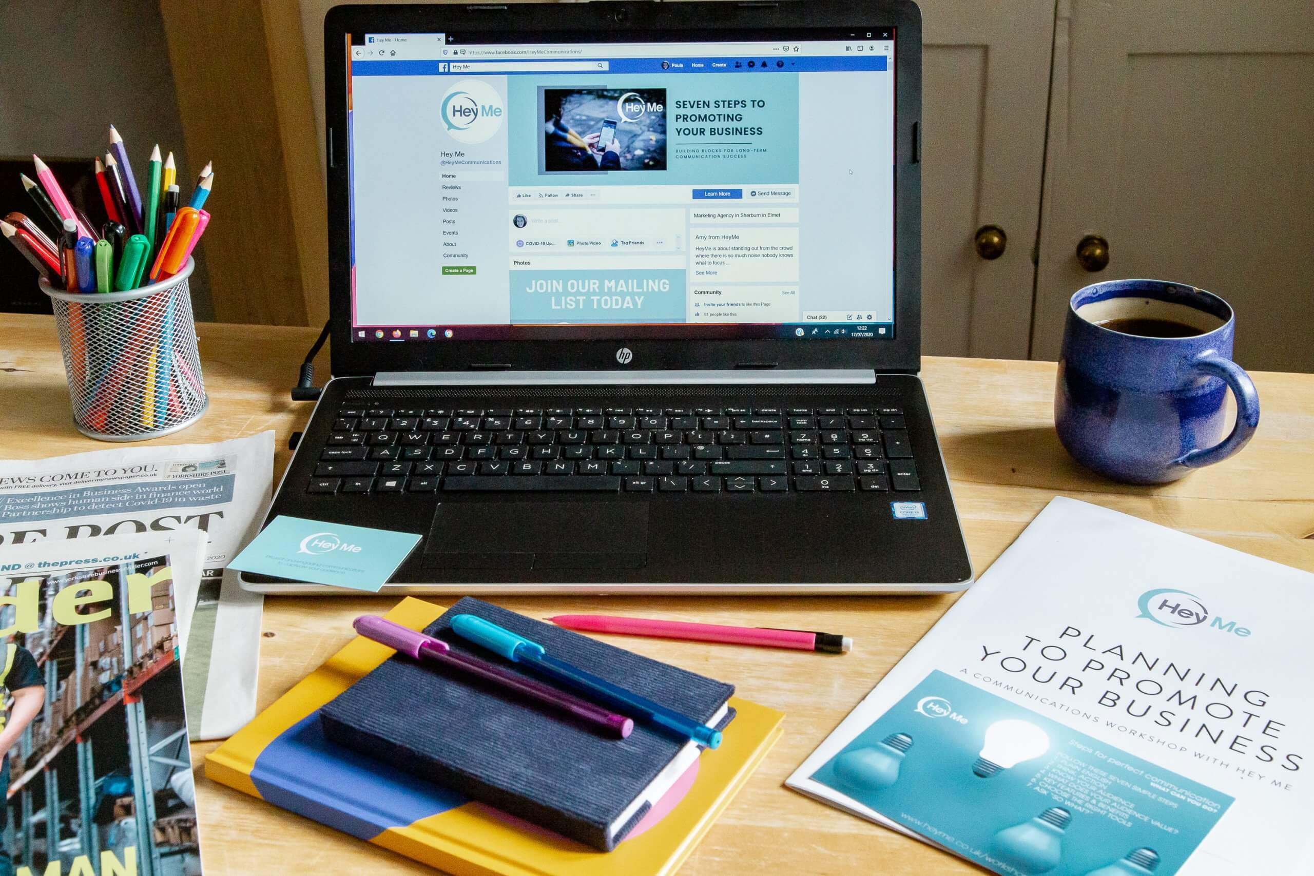 Laptop and Hey Me promotional items on a desk